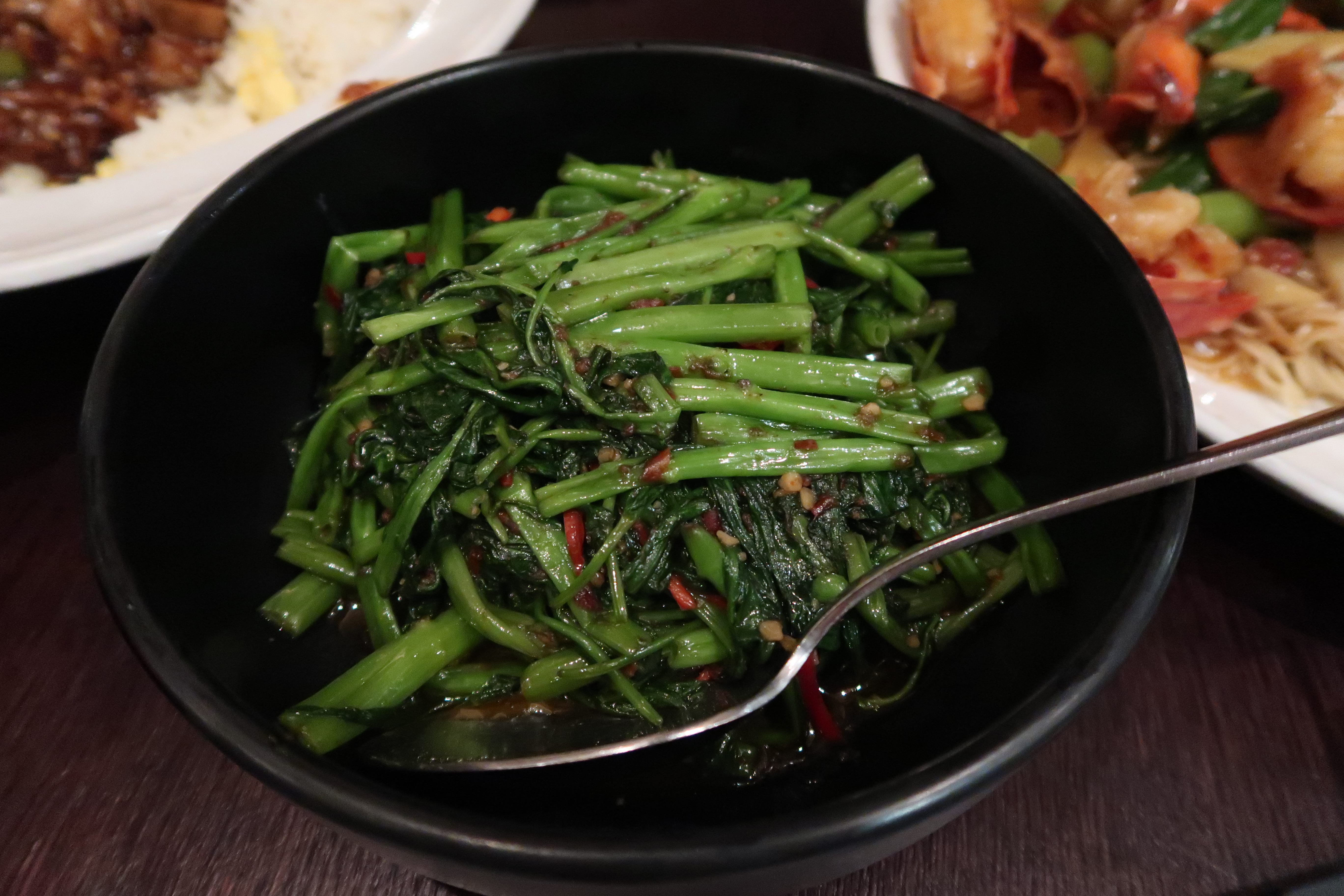 Morning glory vegetables served in a black bowl