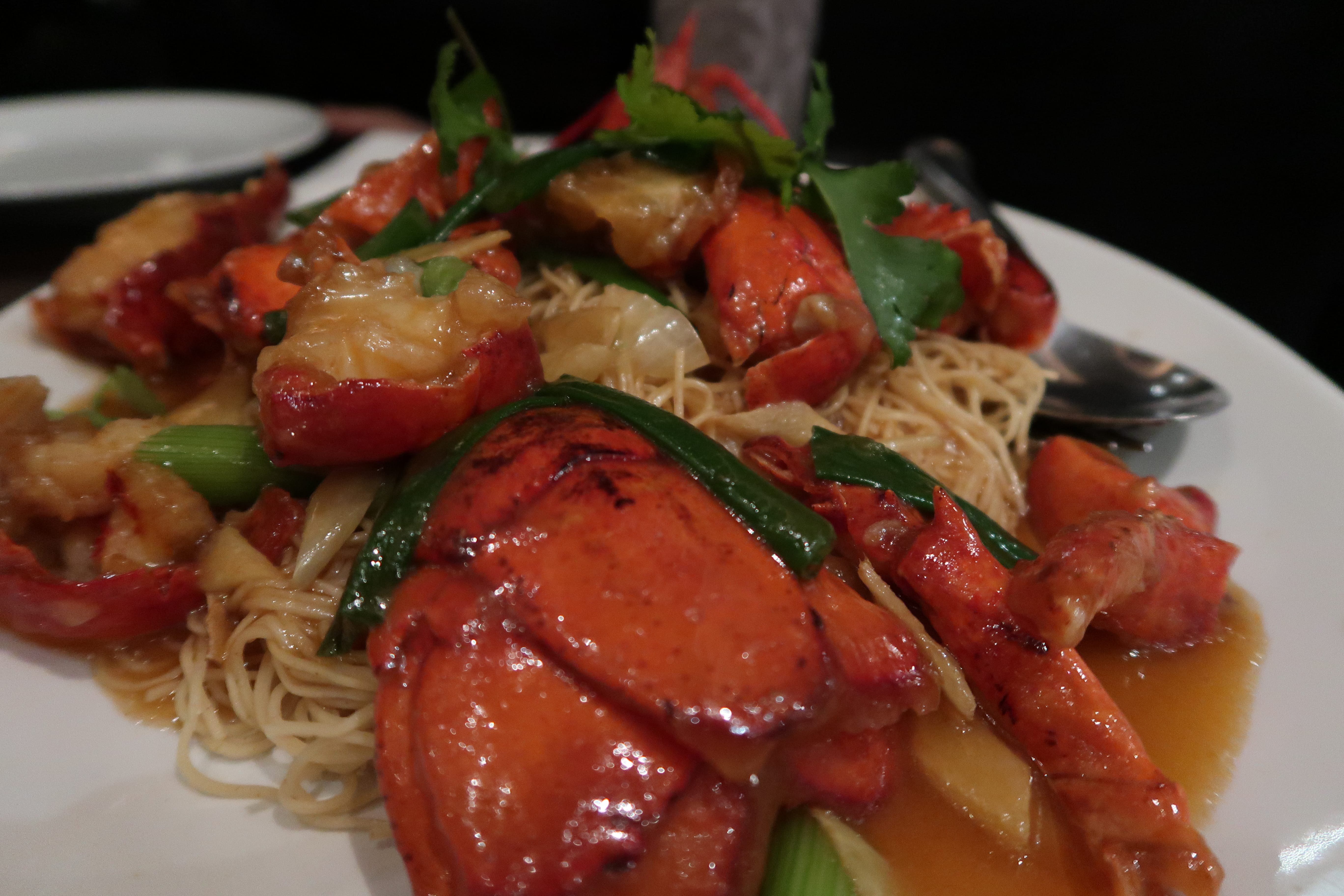 Close up of lobster served on a bed of noodles