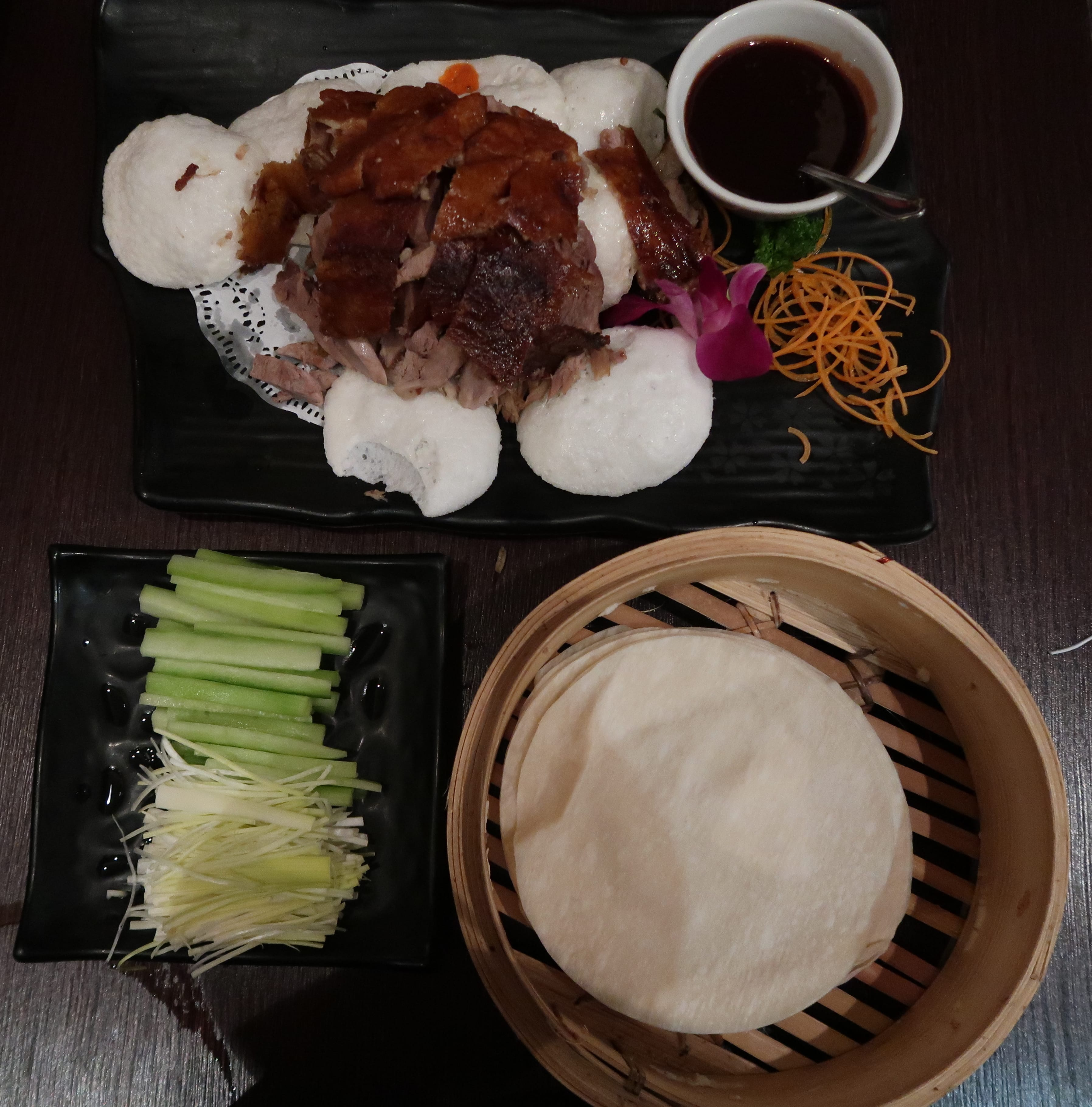Peking duck with cucumber and spring onion garnish with pancakes