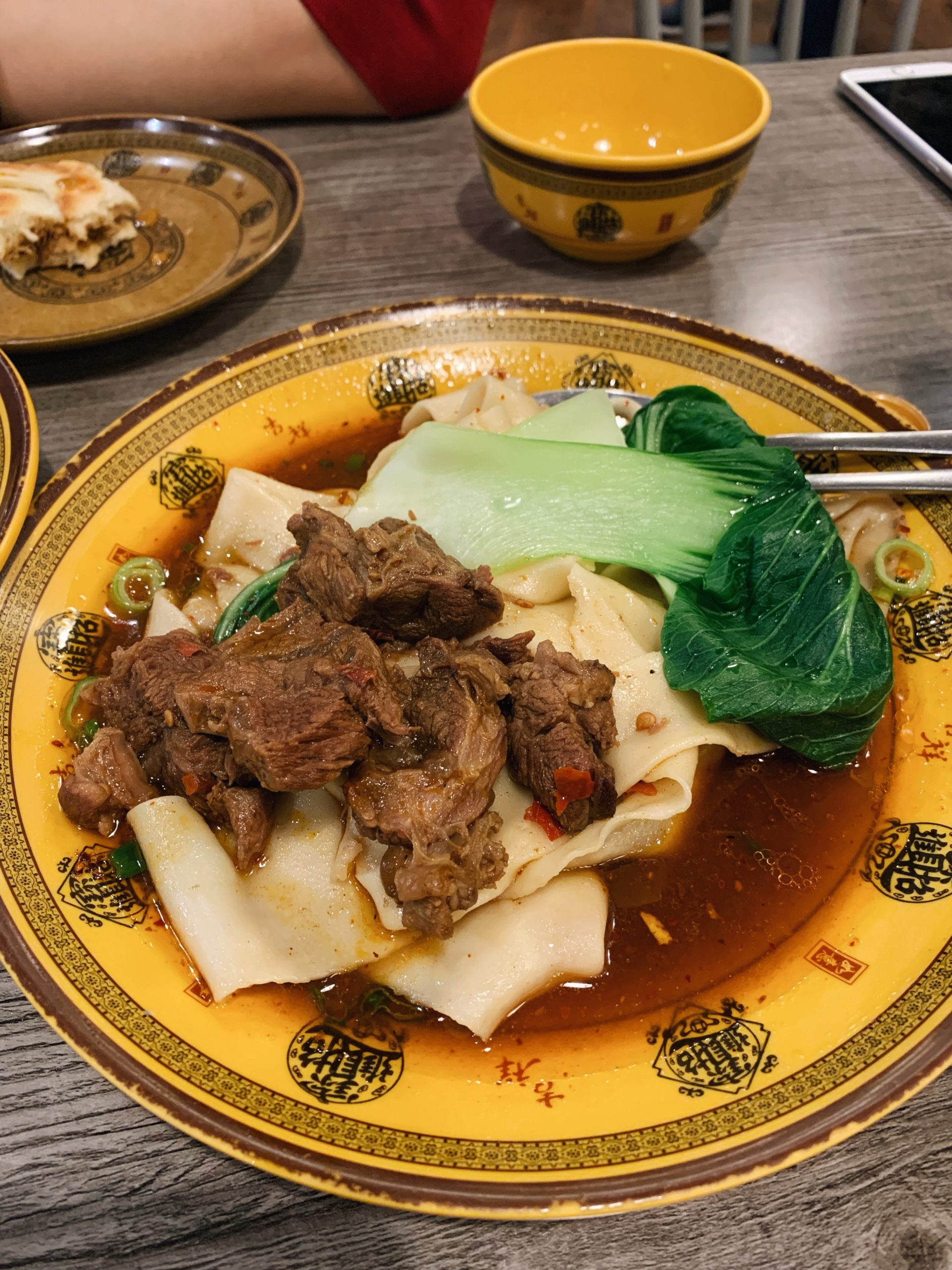 Beef hand pulled noodles served with pak choi on a yellow plate with Chinese characters