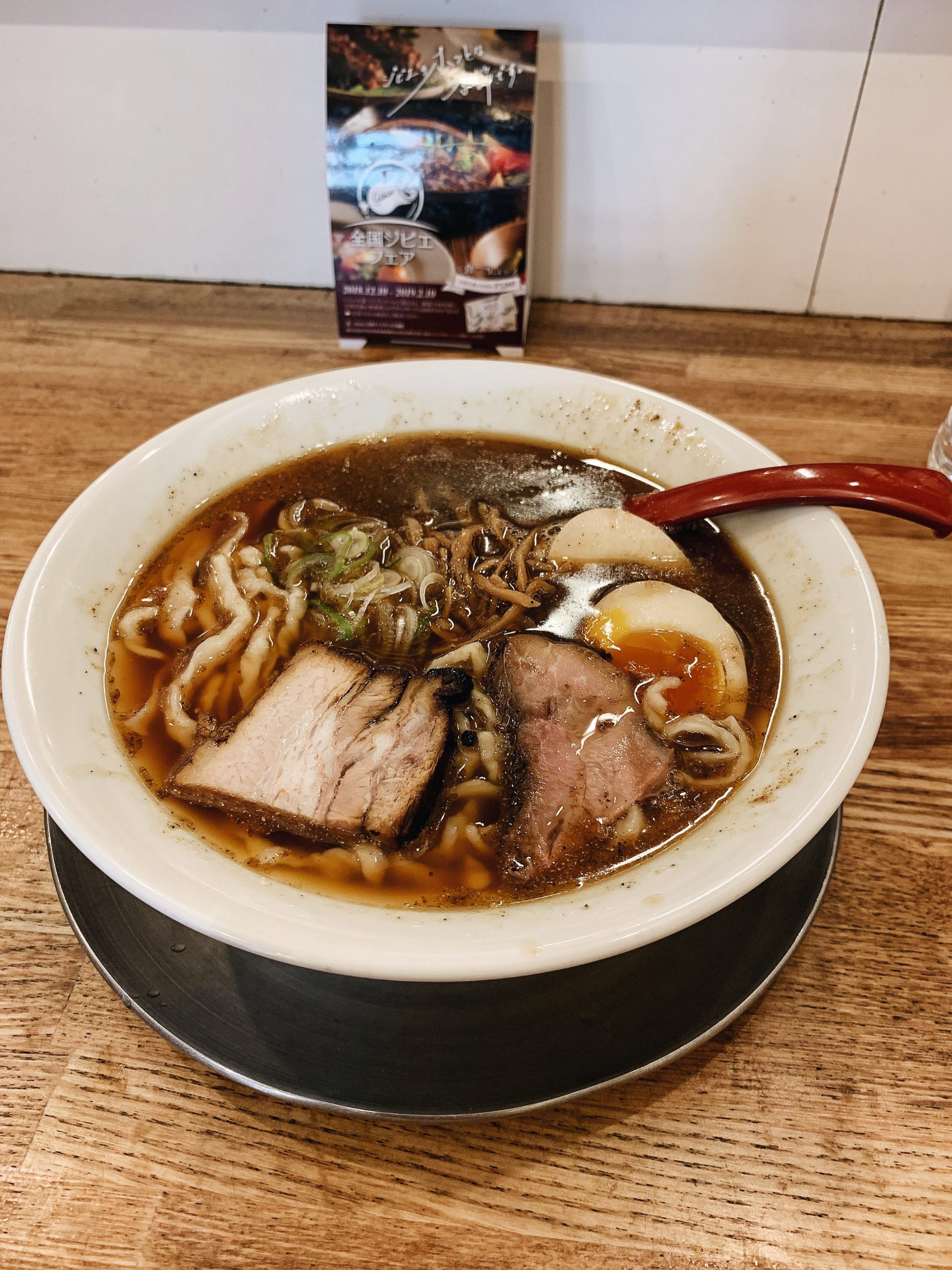 Bowl of ramen with pork slices and boiled egg sliced in half