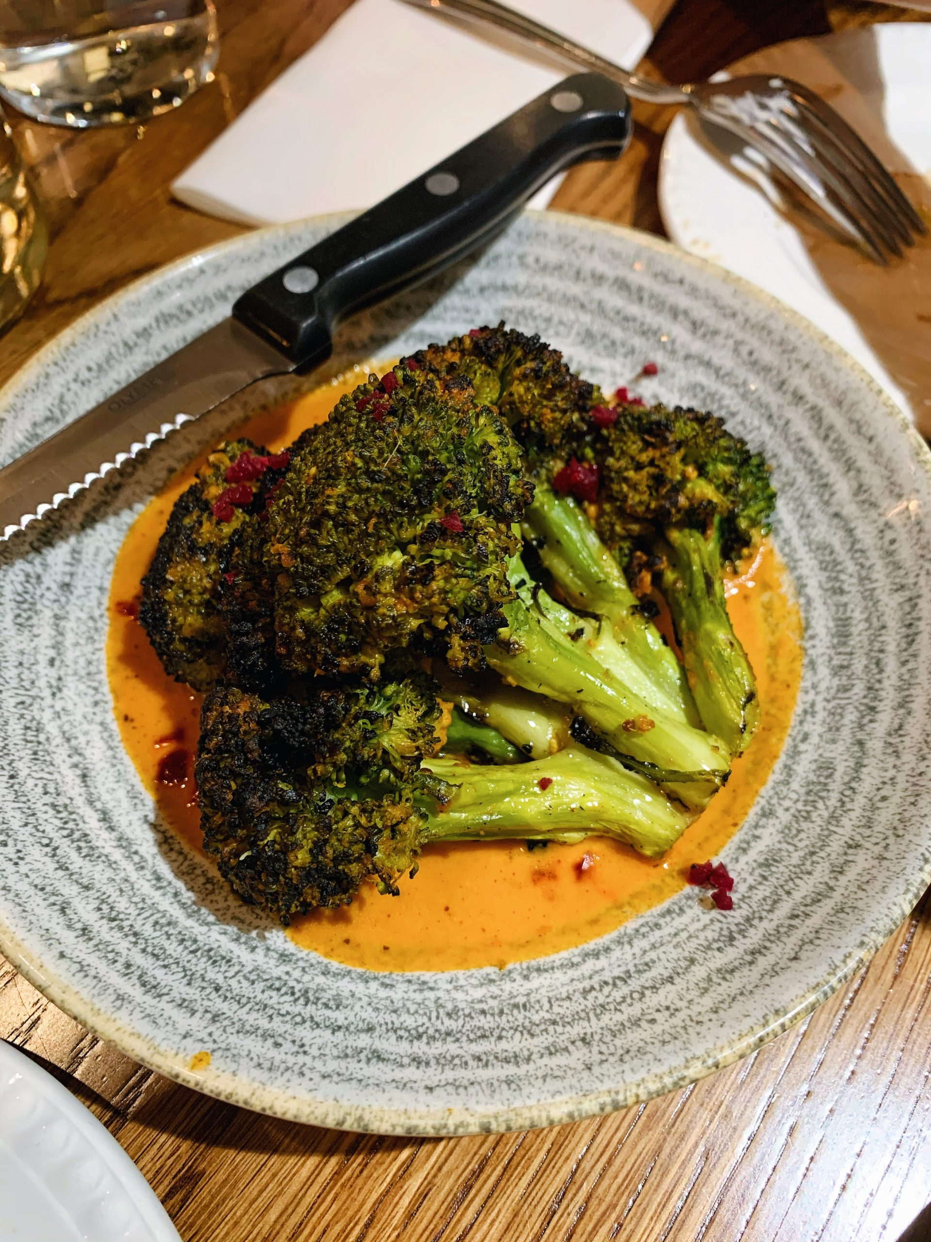 Sigree grilled mustard broccoli served on a bed of orange sauce on a grey circular striped plate